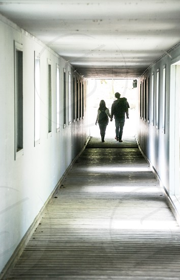 Couple white end bright holding hands silhouette corridor  open together  photo