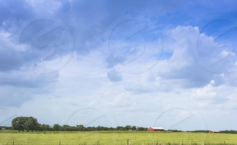 Spring green blue cloud red barns Texas fresh colors farmland rural country road photo