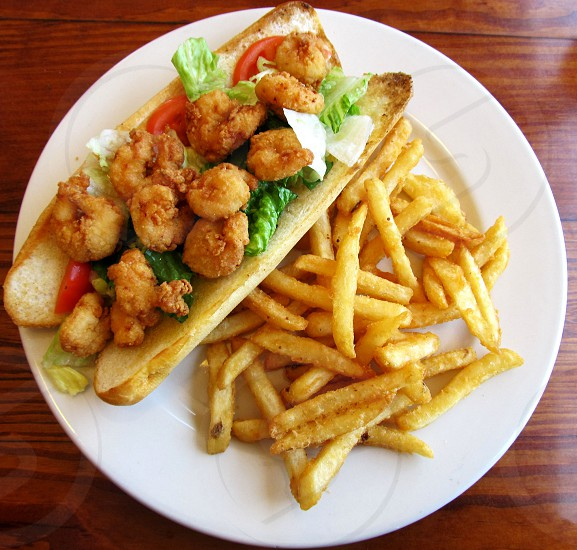 Shrimp poboy and fries on white plate on wooden table photo