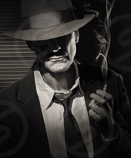 man in black suit and hat smoking gray scale photo