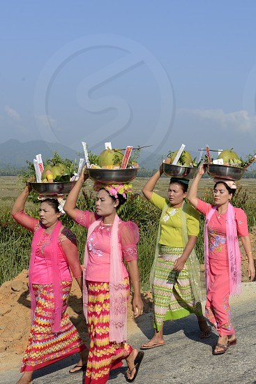 People in traditional dresses at a shinpyu ceremony in a village neat the city of Myeik in the south in Myanmar in Southeastasia. photo