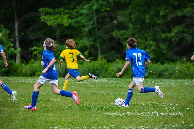 Soccer ball girls running green grass photo