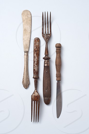 Composition from metalic old knives and forks with wooden handles presented on a gray background with space for text. Vintage Collection. Flat lay photo