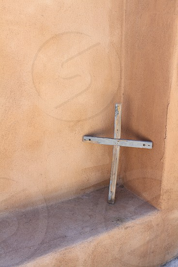 Old crucifix on adobe wall in the southwest photo