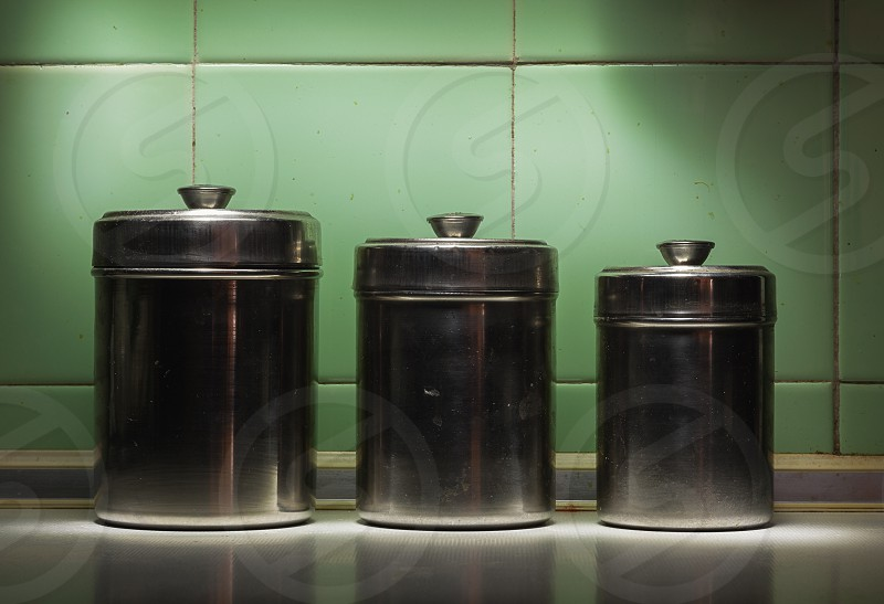Closeup view of three old and dirty metal bowls in front of tiled green wall. photo