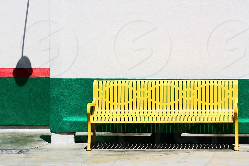 Yellow metal outdoor bench on a white and green wall. photo