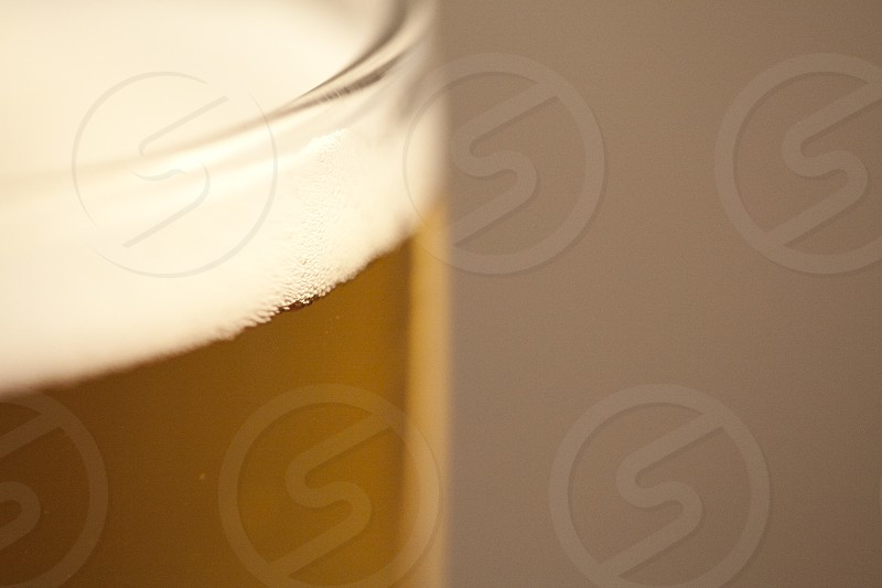 close up photo of clear drinking glass filled with beer photo