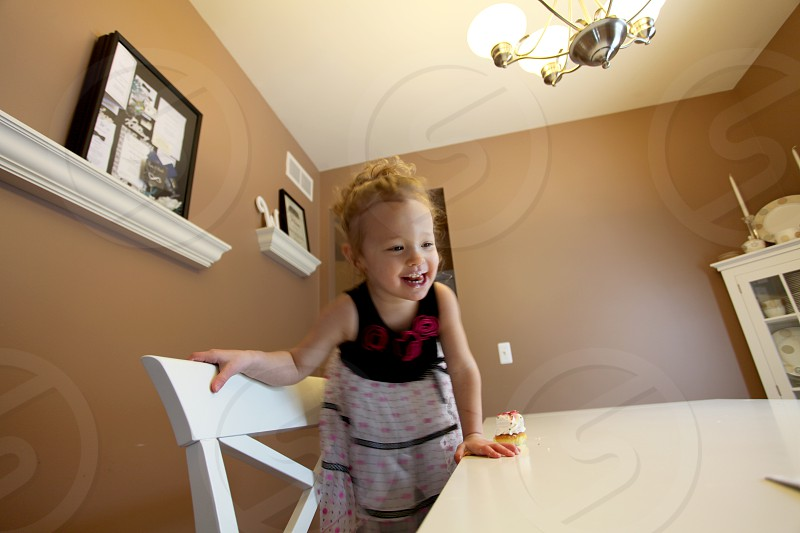 toddler wearing black and white dress on dining table photo