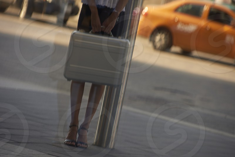A young business woman carrying a silver suitcase through the financial district in Toronto photo