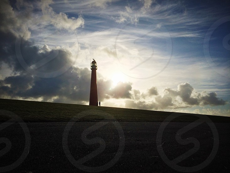 lighthouse silhouette with white clouds background photo