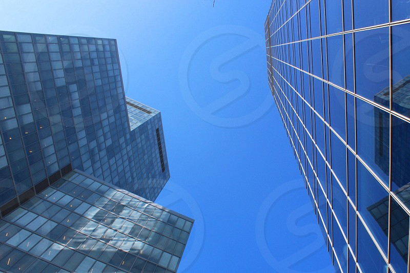low-angle photo of grey and blue highrise building under blue sky at daytime photo
