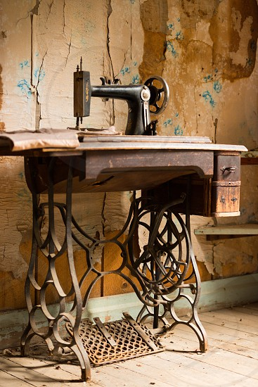 Remnants of colorful wallpaper and a long idle sewing machine are all that is left from a once booming gold rush. photo