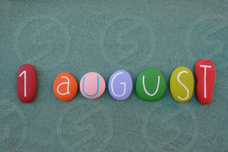 1 August calendar date composed with multi colored stones design over green sand photo