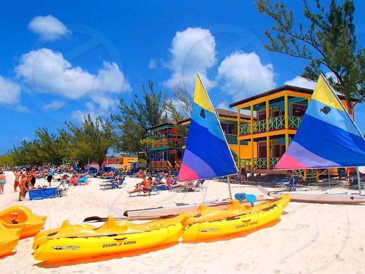 Caribbean sunny day blue sky boats sail boats yellow sand beach cabana photo