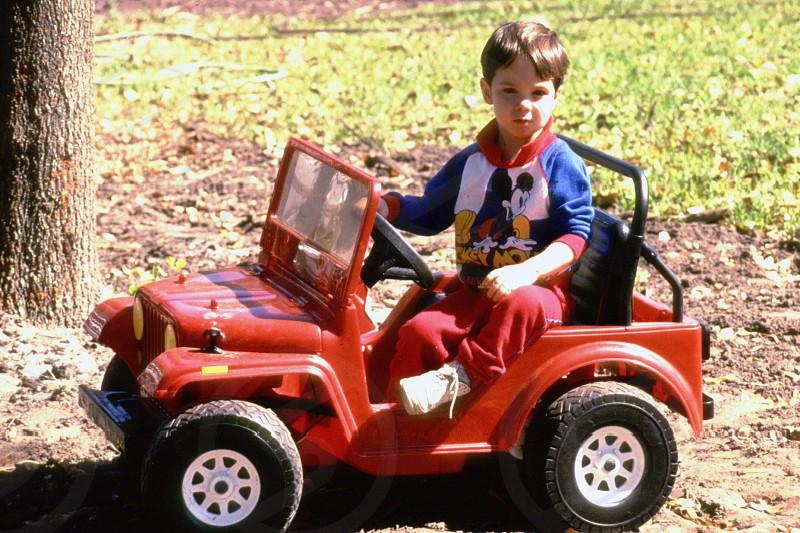 boy riding orange ride on car photo