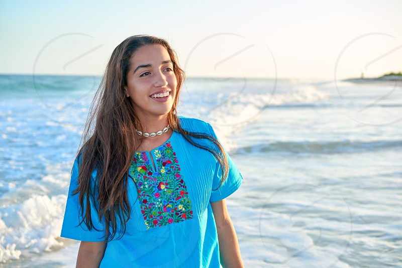 Latin beautiful girl in Caribbean beach sunset with embroidery dress photo