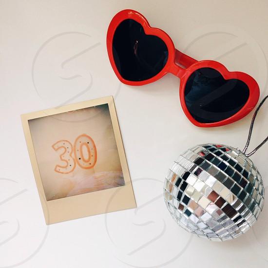 red plastic heart shaped sunglasses and miniature disco ball photo