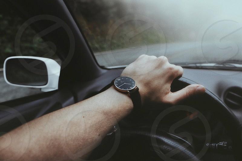 person wearing black analog wristwatch holding black steering wheel inside automobile photo