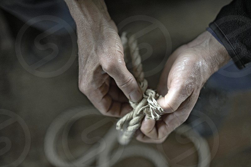 Close up of the hands of an old man tying a knot in a rope photo