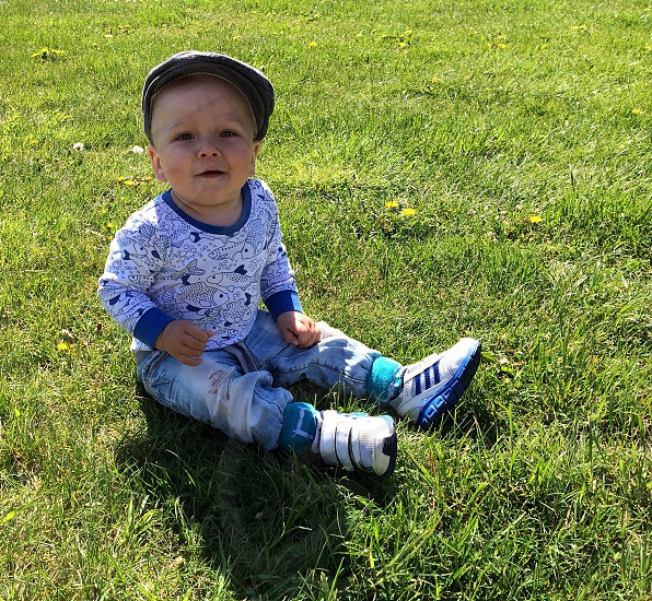 boy in blue sitting on the ground photo