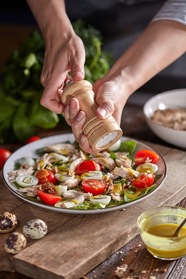 Female hand salt homemade freshly salad from natural organic vegetables meat quail egss in a plate on a wooden table. Concept of healthy diet food. photo