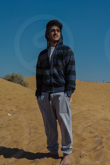 man in blue and black striped zip up hoodie standing photo