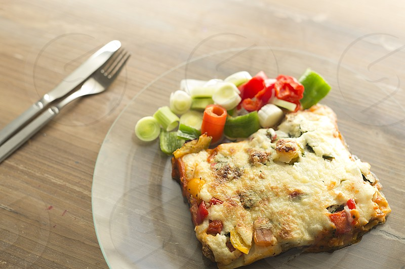 Italian gastronomy called lasagna in a glass dish on a wooden background. photo