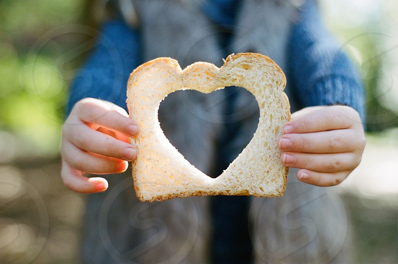 food eating eats bread heart snack kid hands holding photo