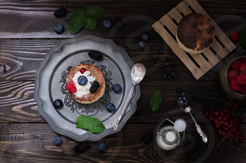Ukrainian cheesecake on old plate with ingredients on dark background photo