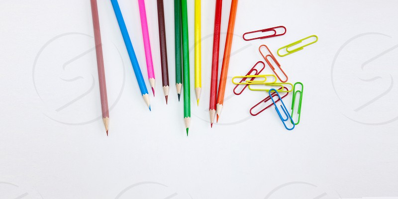 Art and drawing concepts Colored crayon pencils and clips at top corner on white background with copy space. Wide web banner poster brochure template design. Top view Closeup. photo