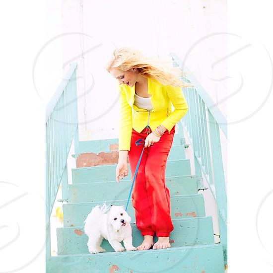 woman in red blazer and red pants with dog standing on staircase photo