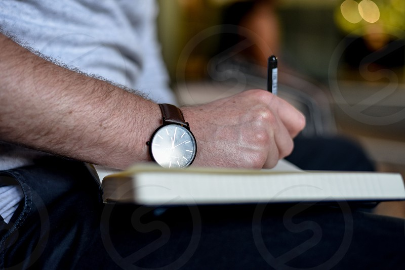 A man writes in his journal in an urban setting. He wears a watch. photo