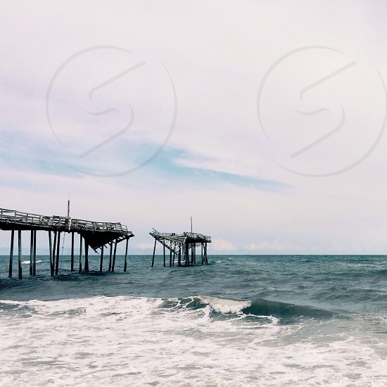 black and white wooden sea port on blue waters photo