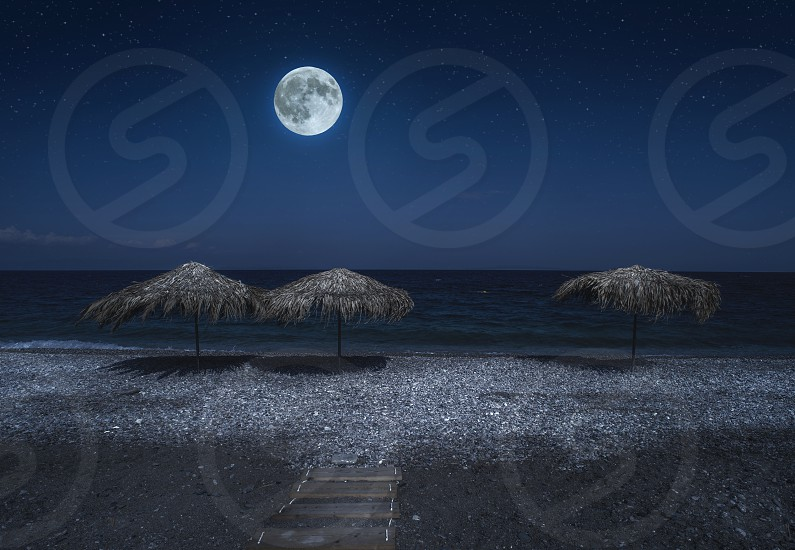 Straw umbrellas on the beach in the night. Moonlight on sea. Night starry sky.  photo
