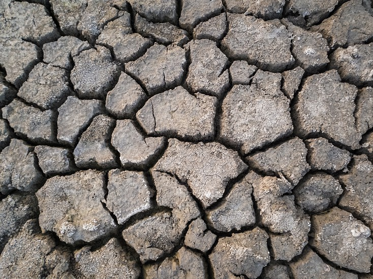 Dry and broken clay ground during drought season concept of global warming problem. Cracked and barren soil texture background. The global shortage of water on the planet. Arid land natural disaster photo
