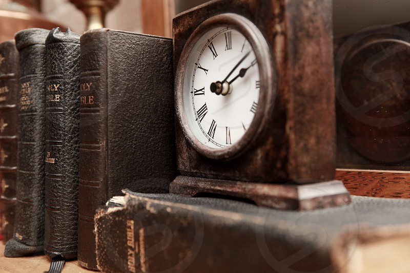 brown silver and white square shaped clock on top of holy bible book photo