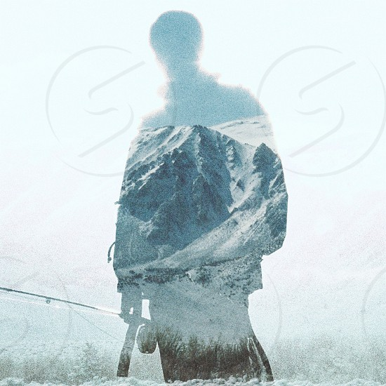 white snow covered grey rocky mountain through a silhouette of a man holding a fishing rod photo