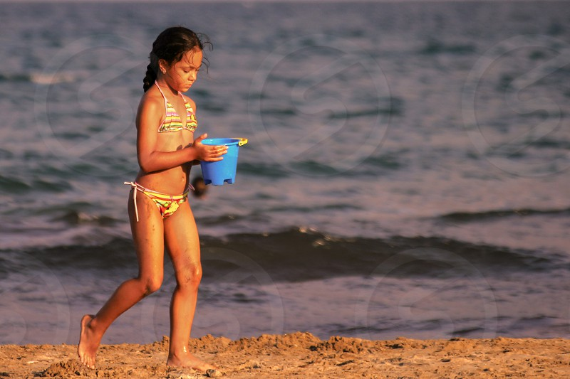 girl wearing yellow halter string bikini carrying blue plastic sand castle maker bucket during sunset photo