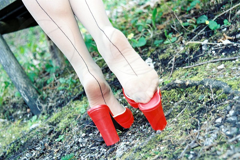 woman wearing white stockings with black lined at the center and red chunky heeled slide sandals photo
