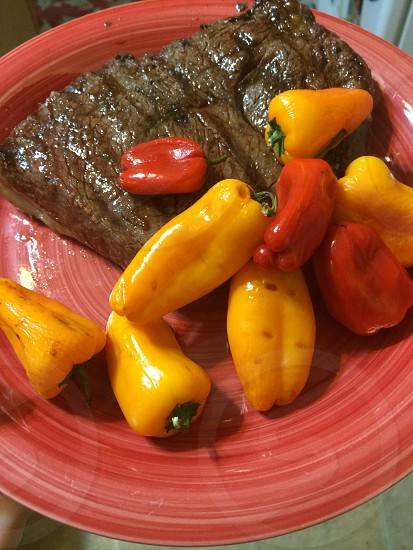 Steak and peppers dinner on red plate  photo