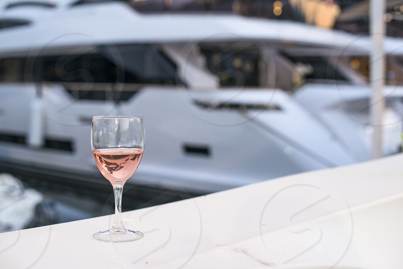Glass of rose wine and a yacht on the background photo