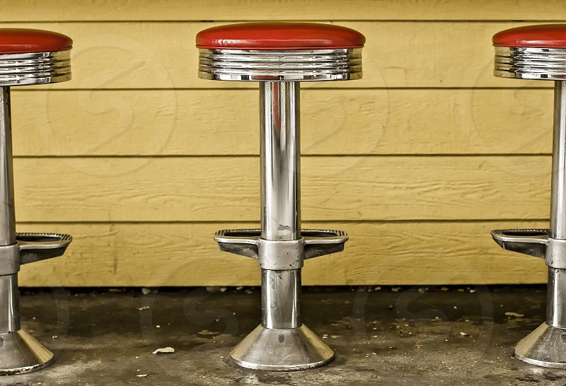 Classic art deco diner stools with red seats against a yellow wood siding background. photo