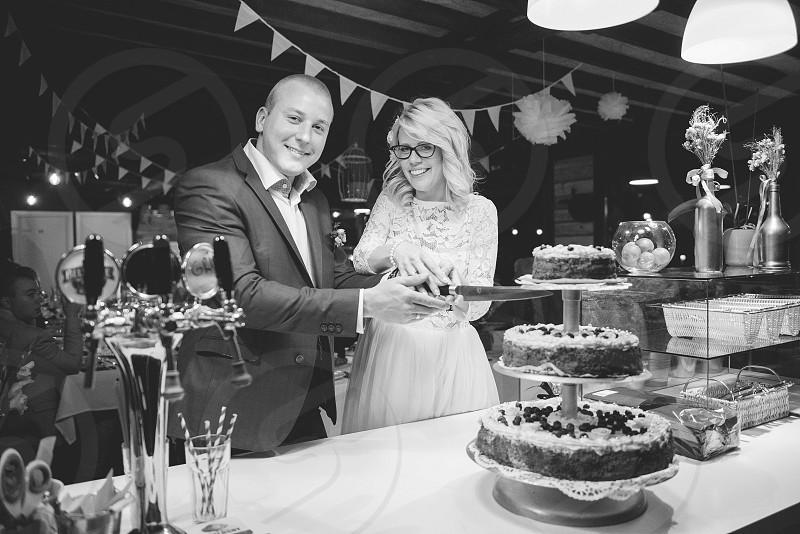 Newly married couple with knife cut wedding cake photo