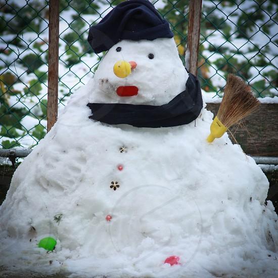 snowman with broom stick hand photo