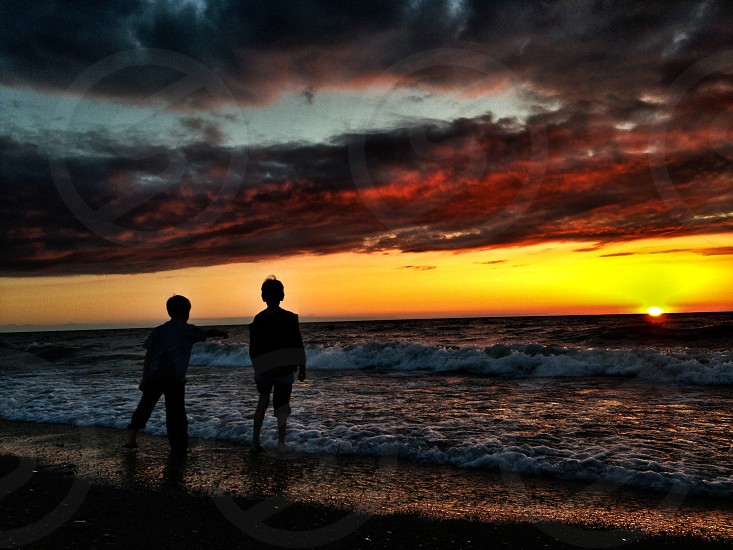 children silhouettes near seashore photography  photo
