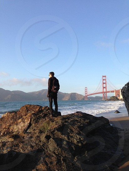 man carrying brown backpack standing on rock near golden gate bridge photo