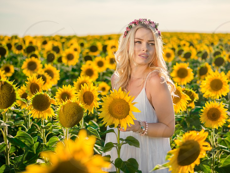 Young beautiful blonde woman standing in sunflower field. Sunset background. Sexy sensual portrait of girl in flowers wreath and white summer dress. photo