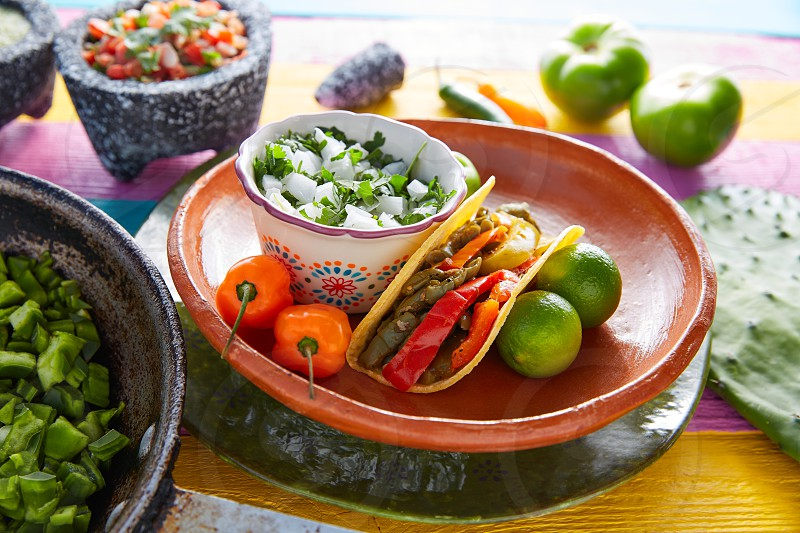 Nopal taco mexican food with chili pepper and ingredients on colorful table photo