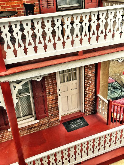 brown and red brick house with red balcony and white fences photo