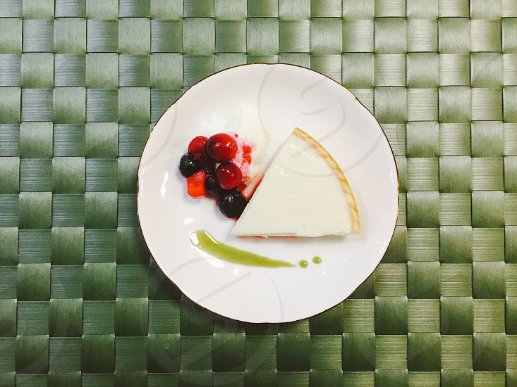 crusted pie slice next to red and black berries and splash of green sauce on white ceramic plate photo